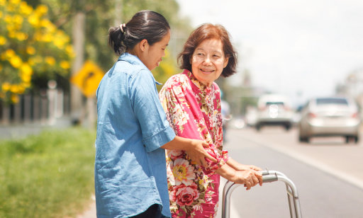young woman assisting senior woman crossing the street